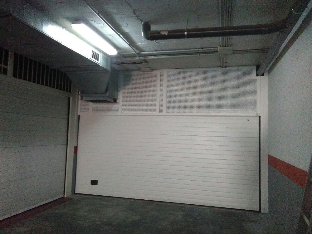Puerta seccional exterior con rejilla de ventilación