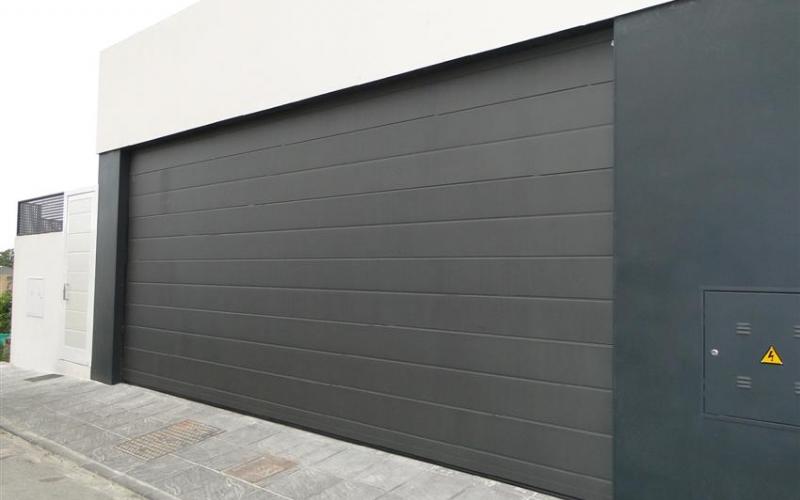 Puerta seccional de apertura vertical con acabado liso