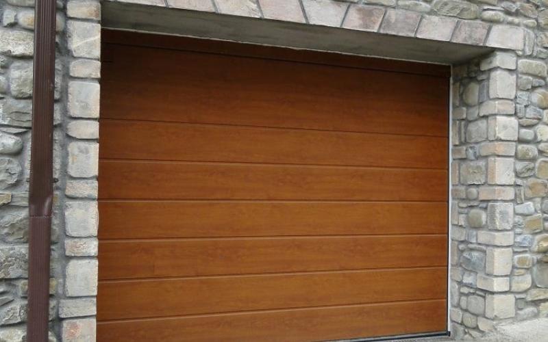 Puerta seccional de apertura vertical y acabado en madera