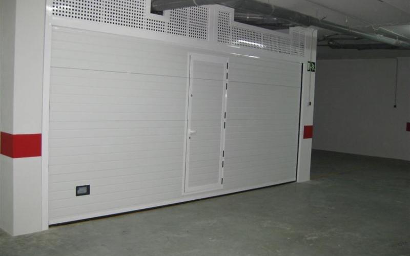 Puerta seccional con apertura vertical y acceso peatonal