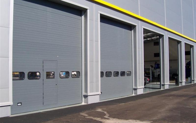 Puerta seccional con puerta peatonal para uso industrial