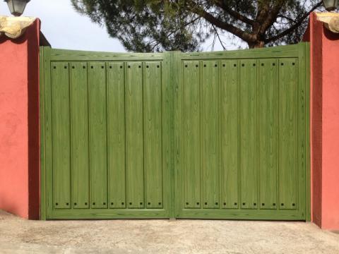Puerta abatible de dos hojas en chapado madera con tachuelas negras