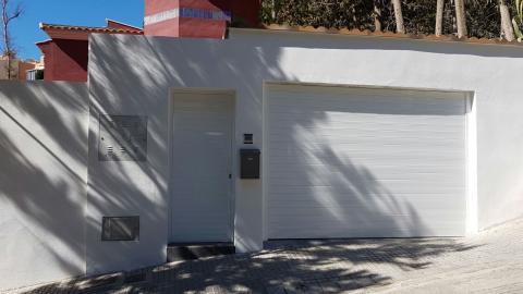Puerta de garaje seccional y puerta peatonal con paneles